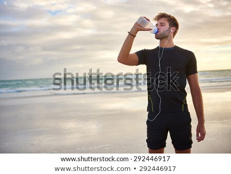 Stock photo: Young sports man standing on the beach drinking water listening music.