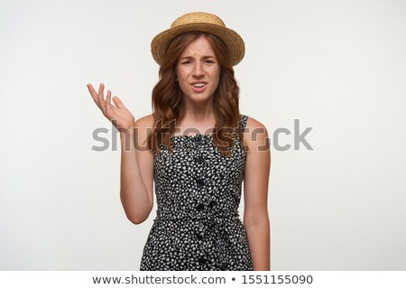 Portrait of surprised curly woman 20s wearing dress frowning whi Stock photo © deandrobot