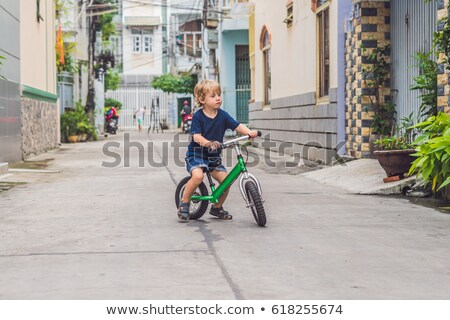 active blond kid boy driving bicycle n the street of the city toddler child dreaming and having fun stock photo © galitskaya