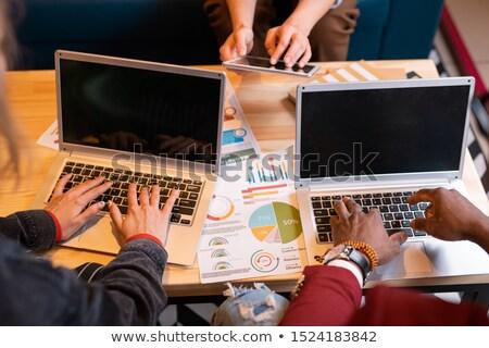 Hands of intercultural students pressing keys of laptop keypads Stock photo © pressmaster