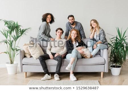 Joyful intercultural teenagers in casualwear relaxing on sofa together Stock photo © pressmaster