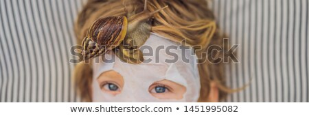 Strongly younger from the mask with snail mucus. A child in a mask for the face with a snail. Snail  Stock photo © galitskaya