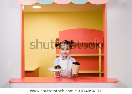 Cute little girl holding glass of drink and plate with berry cake or dessert Stock photo © pressmaster