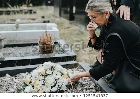 Man and woman on a cemetery with flowers Stock photo © Kzenon