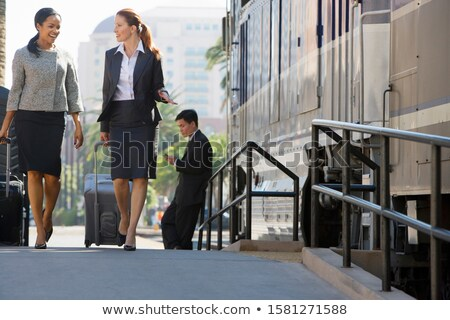 Asian traveler woman waiting for travel on railway platform. Businesswoman standing with luggages at Stock photo © Maridav