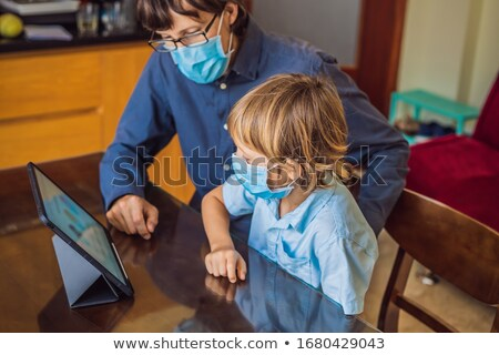 Boy studying online at home using laptop. Father helps him learn. Studying during quarantine. Global Stock photo © galitskaya