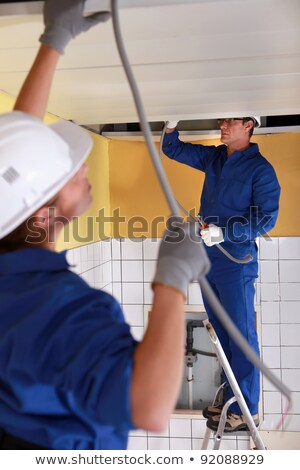 Stock fotó: Two Electrician Feeding Length Of Cable Through Ceiling