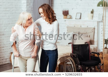 Smiling senior woman walking with crutches Stock photo © stockyimages