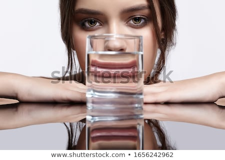 Young woman drinking a glass of water on a mirrored table Stock photo © photography33