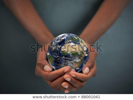 feminine hand holding the earth against a dark background stock photo © wavebreak_media