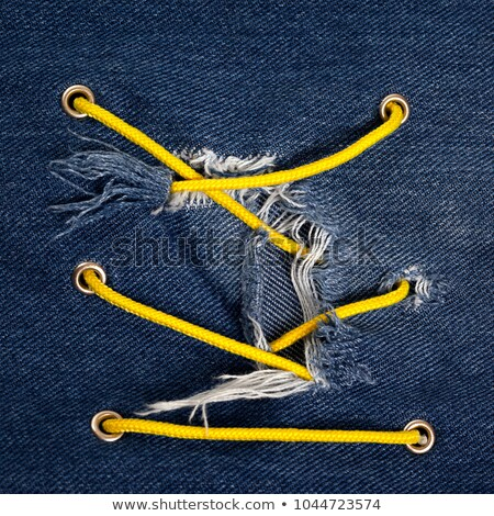 Blue jean with hole and crisscross yellow lacing Stock photo © BSANI