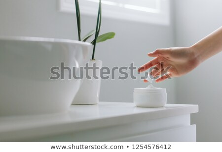 Foto stock: Young Woman Applying Beauty Product