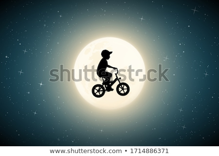 silhouette of lonely young boy riding bicycle stock photo © xuanhuongho