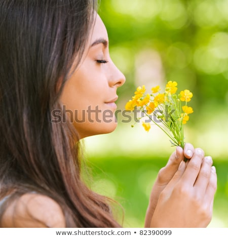 Young beautiful girl smells flowers, against green summer garden Stock photo © nenetus