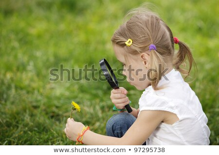 pretty little girl with magnifying glass looks at flower stock photo © paha_l