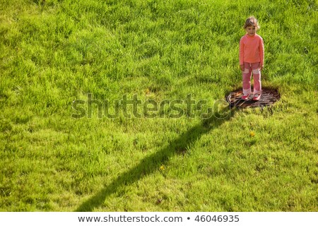 Little girl is standing on water drain hatch in grass field. girl in right upper corner. long shadow stock photo © Paha_L