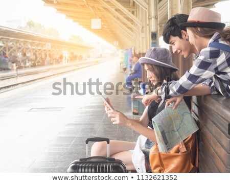 smiling seated woman with tablet pointing finger  Stock photo © feedough