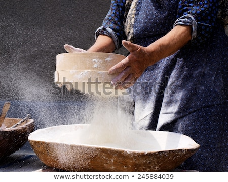 Woman sieving flour from the bowl on the wooden board Stock photo © wavebreak_media