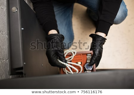 Stock photo: thief stealing valuables from safe at crime scene