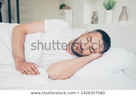 portré · fiatalember · alszik · ágy · hálószoba · kéz - stock fotó © dashapetrenko