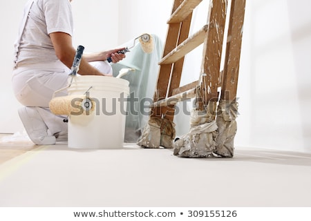 Zdjęcia stock: Worker Painter Paints Wall At The Bottom