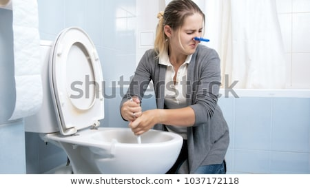 Cleaner woman cleaning mirror in restroom Stock photo © Kzenon
