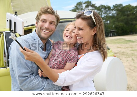 family taking photo by selfie stick at camp stock photo © dolgachov
