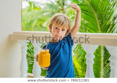 the boy holds mason jar of mango smoothies in his hand and shows how he grew up thanks to vitamins a stock photo © galitskaya