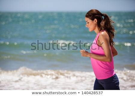 Stock photo: Young woman jogging on the beach in summer day. Athlete runner exercising actively in sunny day