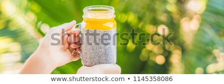 chia seed pudding with almond milk and fresh mango topping in hand stock photo © galitskaya