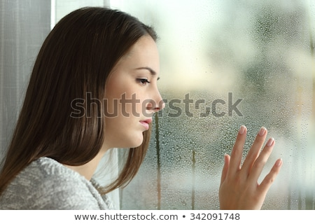 Sad woman looking the rain falling through a window at home or hotel Stock photo © artfotodima