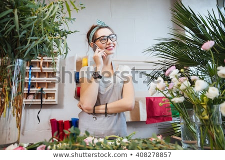 Cheerful young woman gardener talking on mobile phone Stock photo © deandrobot