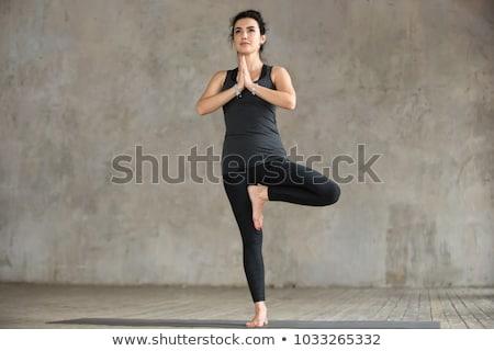 young woman doing yoga tree pose at studio Stock photo © dolgachov