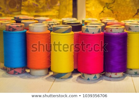 Background with a lot of colorful coils with threads. Bobbins are stacked in three rows, one on the  Stock photo © galitskaya