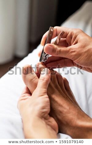 young caucasian man cutting his toenails Stock photo © nito