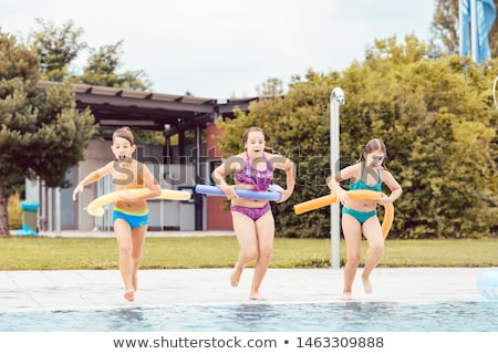 Friends running with inflatable tube Stock photo © Kzenon