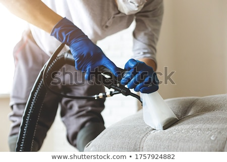 Man Cleaning Sofa With Vacuum Cleaner Stock photo © AndreyPopov