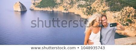 blond tourist in mallorca beach taking beach photo stock photo © lunamarina
