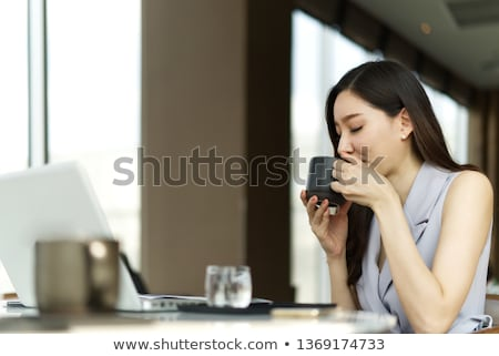 A young girl is sitting at the table in the office, holding a red cup in her hands and looking at th Stock photo © Traimak
