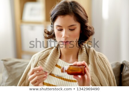 sick woman with antipyretic or cough syrup at home Stock photo © dolgachov