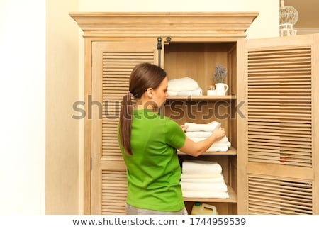 Woman wearing green t-shirt near cupboard holding towels in laun Stock photo © dashapetrenko