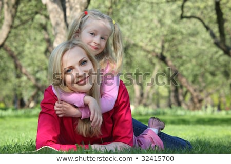 daughter embraces behind mother lying on grass in park Stock photo © Paha_L