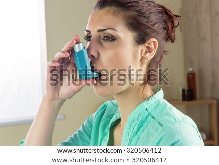 Close up image of a young woman using inhaler  Stock photo © Lopolo