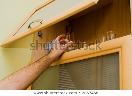 Man getting a glass out of the cupboard Stock photo © photography33