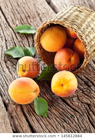 Fresh apricots with leaves in basket on wooden table Stock photo © yelenayemchuk