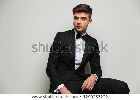 attractive groom in black tuxedo sitting on a wooden chair  Stock photo © feedough