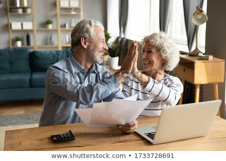 Smiling mature couple giving high-five Stock photo © Kzenon
