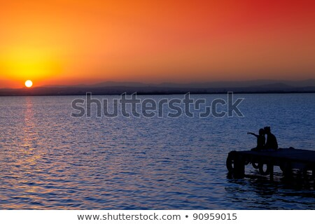Stock photo: Mother and daughter sitting on dock