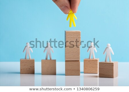 Hand Holding Human Figure Over Stacked Block Stock photo © AndreyPopov