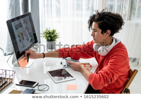 Young male designer with color swatches putting sticky notes on computer Stock photo © pressmaster